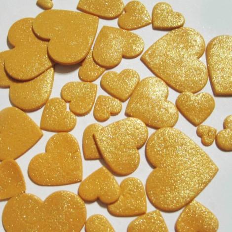 Auksinės spalvos blizgančios skirtingo dydžio širdys